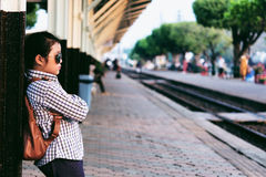 Cute girl in train station waiting to travel. Summer holiday. Stock Photo