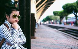 Cute girl in train station waiting to travel. Summer holiday. Royalty Free Stock Photos