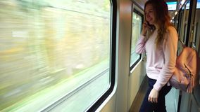 Cute girl traveler rides train and chatters on  phone, standing near large transport window. Beautiful young woman talking on cellphone and smiling, looking at stock footage