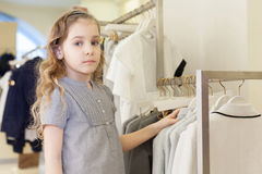 Cute girl tries on a dress in a store Stock Image