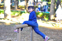 Cute girl try to reach higher plank at playground. A cute girl stretches her legs to reach higher plank at the playground Stock Image