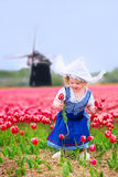 Cute girl in tulips field with windmill in Dutch costume. Adorable curly toddler girl wearing Dutch traditional national costume dress and hat playing in a field Stock Images