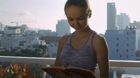 Cute Girl Turns over Diary Pages on Roof Terrace. Closeup cute girl makes notes and turns over diary pages on rooftop lounge terrace against city skyscrapers in stock video