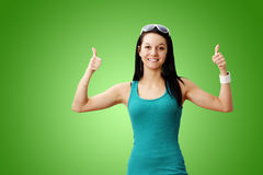 Cute girl two thumbs up. Pretty healthy and lean young woman smiling giving two thumbs up over gradient green background: perfect for weight loss or other Royalty Free Stock Photo