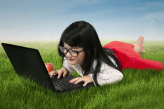 Cute girl typing on laptop at field Royalty Free Stock Images