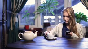 Cute girl typing message on smart phone in cafe. Smiling blonde teenage female texting on cell phone while sitting in modern coffee shop and drinking tea stock footage