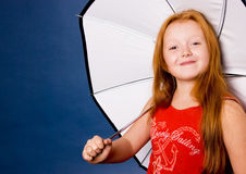Cute girl with an umbrella. Cute ginger girl with an umbrella royalty free stock photo