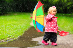 Cute girl with umbrella in raincoat and boots outdoor Royalty Free Stock Photos