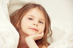 Cute girl under a blanket in bed in the bedroom. Lying on bed. royalty free stock image