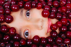 A cute girl under many pieces of cherry. A cute girl under many red cherry Royalty Free Stock Photos