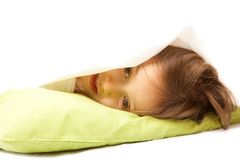 Cute girl under the pillow looking out Royalty Free Stock Image
