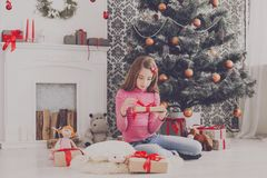 Cute girl unwrapping christmas presents Stock Image