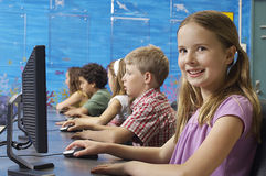 Cute Girl Using Computer. Portrait of a happy cute girl with classmates sitting in computer lab Royalty Free Stock Photos