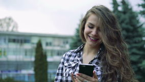Cute girl using phone, smiling by nice background stock video footage