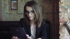 The cute girl using a tablet in a modern comfortable cafe 4k stock video footage