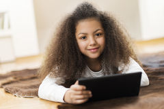 Cute girl using a tablet. Sitting Royalty Free Stock Photography