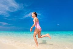 Cute girl on vacation. Happy girl running and splashing at shallow water at beach having a lot of fun on summer vacation Stock Photography