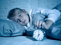 Cute girl waking with alarm clock feeling tired and angry time to go to school early in the morning royalty free stock photos