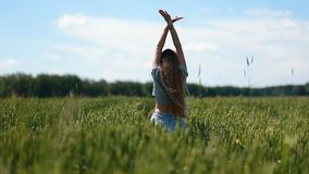 Cute girl walking on green field with open arms stock footage