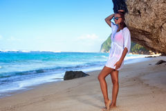 Cute girl walking at tropical beach bali. Posing near a rock Stock Image