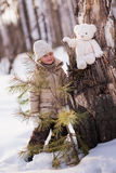 Cute girl walking in the winter woods with her toy. Bear sits on the stump. Stock Photos