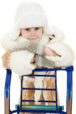 Cute girl in warm clothes with a sled Royalty Free Stock Photo