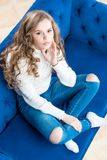 Cute girl in a warm sweater on the couch in the living room view Royalty Free Stock Photography