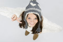 Cute girl in warm winter clothes making victory sign. Stock Photo