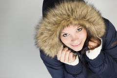 Cute girl in warm winter jacket looking up and smiling. Royalty Free Stock Images