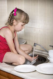 Cute girl washing the dishes Royalty Free Stock Photo