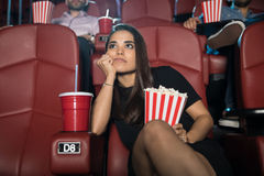 Cute girl watching a boring movie. Attractive young brunette looking really bored at the movie theater Stock Images