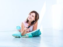 Cute girl watching TV lying. On the floor stock photography