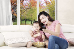 Cute girl watching tv with mother Stock Photo