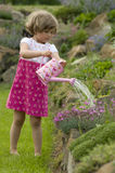 Cute girl watering flower in the garden Stock Images