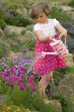 Cute girl watering flower in the garden Royalty Free Stock Photos