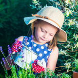 Cute girl watering herbs. Child taking care of plants. Kid with Royalty Free Stock Photo