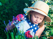Cute girl watering herbs. Child taking care of plants. Kid with. Water can. Little gardener with lavender and rosemary Stock Photo