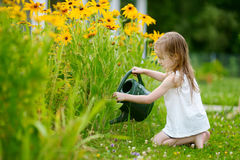 Cute girl watering plants in the garden Royalty Free Stock Photos