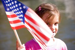 Cute girl waving flag. A young girl who was waving a flag and I caught her peeking around it royalty free stock photo