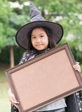 Cute girl wear witch dress show picture frame Royalty Free Stock Photography