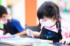 Free Cute Girl Wearing A White Cloth Face Mask. Students Were In The Water Painting Class. Pupil Kid Wear An Black Apron. Royalty Free Stock Photography - 209432807
