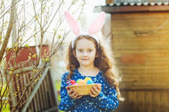 Cute girl wearing bunny ears holding a basket with Easter eggs. Royalty Free Stock Photo