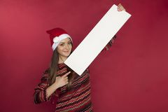Cute girl wearing a Christmas hat is holding a place for the ad. On the red background Stock Photo