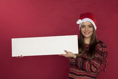 Cute girl wearing a Christmas hat on a red background holding a. Place for the ad, on the red background Stock Photography
