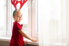 Cute girl wearing costume reindeer antlers, standing by the window. Cute girl wearing costume reindeer antlers, standing by the window, impatiently waiting for stock image