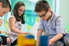Cute girl playing next to her colleague in the classroom of a mo. Cute girl wearing eyeglasses while playing with concentration a creative game next to her royalty free stock photos