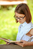 Cute girl wearing eyeglasses reading unteresting book Stock Photos