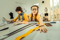 Cute girl wearing glasses taking paper with sketches. Paper with sketches. Cute girl wearing glasses and accessories taking paper with sketches royalty free stock image