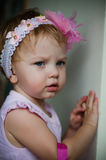 Cute girl wearing head band. Portrait of sad, cute young girl wearing headband Royalty Free Stock Photos