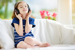 Cute girl wearing huge wireless headphones. Pretty child listening to the music. Schoolgirl having fun listening to kid`s songs at Royalty Free Stock Photography